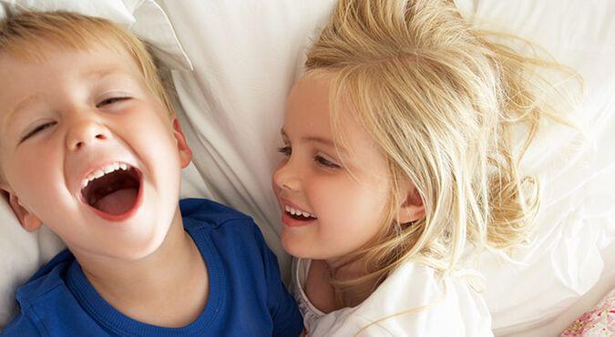 Hermanos acostados en la cama