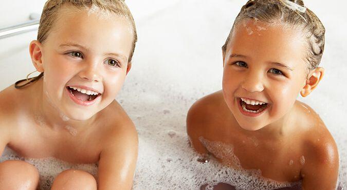Hermanos felices tomando un baño de espuma