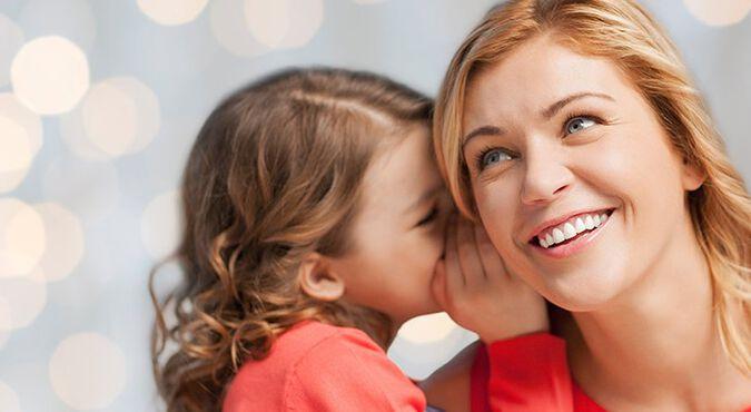 Niña le cuenta un secreto a su madre